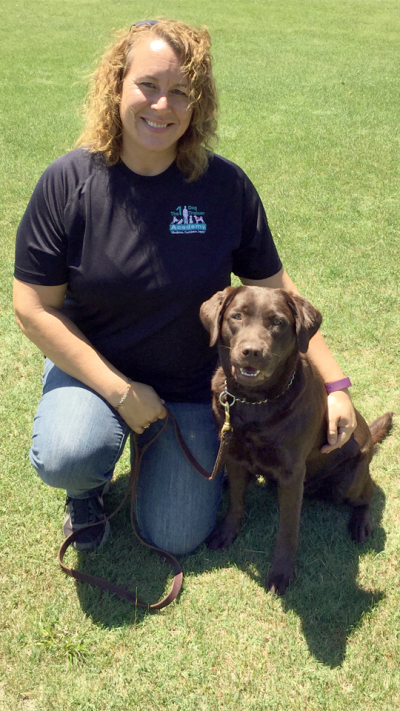 Our Senior Trainer, Cori Mitchell, poses with a brown dog named Ziva.