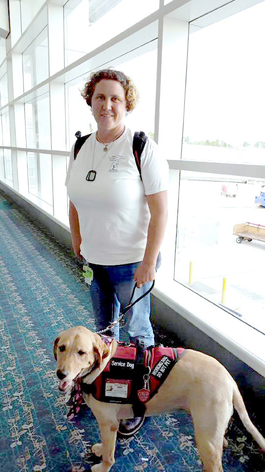 Professional dog trainer Sharon Burch stands in an airport terminal with a yellow labrador wearing a red service animal vest.