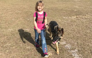 A young girl named Cami is walking her friend, a German Shepherd dog named Linux.